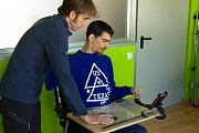 Performing an usabilitity test. Researcher standing and user in wheelchair using a smarthphone